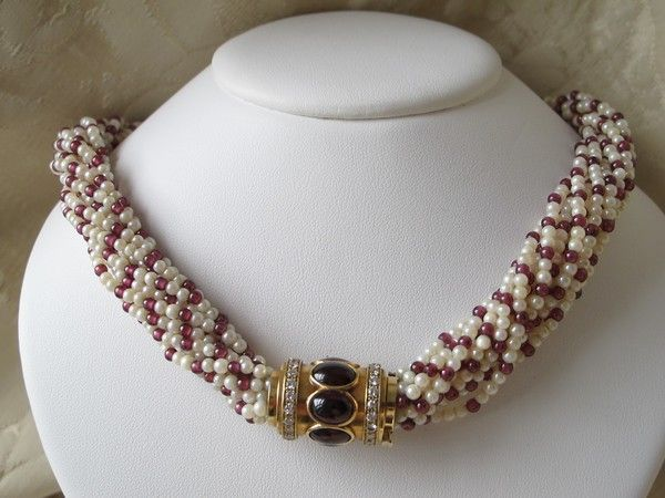 Natural seed pearl and Ruby necklace with a Diamond and Garnet cabochon closure, set in eighteen karat yellow gold