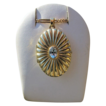 Oval medallion made of fourteen karat yellow gold with a blue Topaz in the center