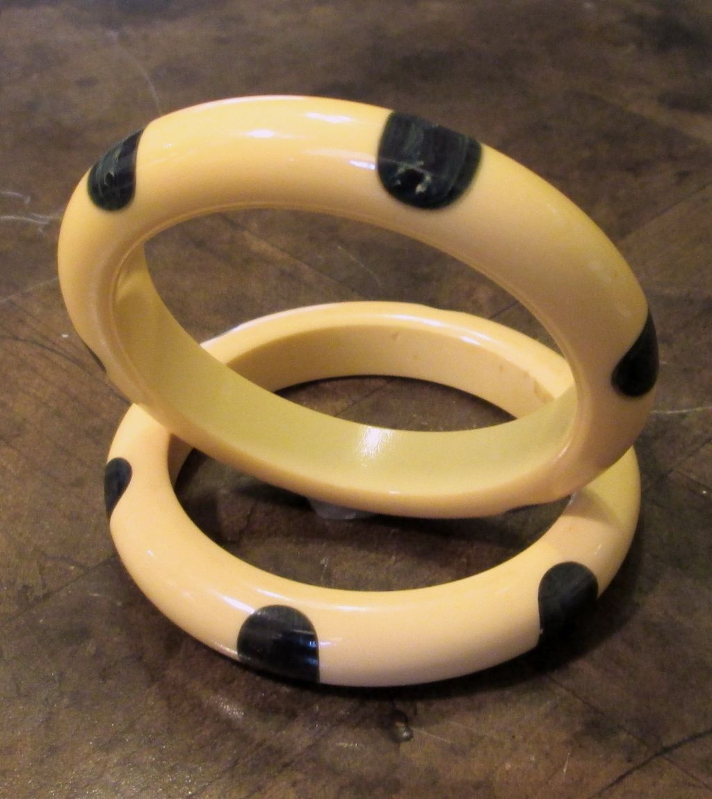 A Pair Of Polka Dot Bakelite Bangles In Cream With Dark Green Dots, Circa 1930