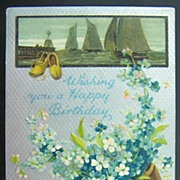1909 Silvered Litho Postcard, Dutch Clogs Overflowing with Forget-me-nots, Sailboat Inset