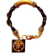 A Unique Pendant Adorns Black Leather Bracelet with Bronze