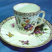 Fine Porcelain Demi Tasse and Saucer with Hand Painted Flowers.