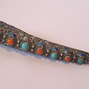 Chinese export silver pin decorated with enamel and real stones.