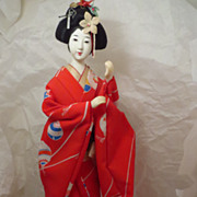 Geisha in Red Kimono on Wooden Stand