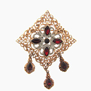 Gold tone vintage brooch with dangles and red stones