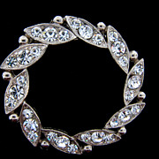 Large circular heavier brooch with colorless rhinestones