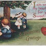 Forlorn Little Boy Sitting under a Tree as boy and Girl Kiss Valentine Vintage Postcard