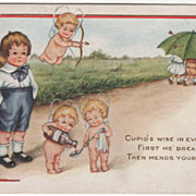Four Cupids Helping a Forlorn Little Boy Valentine Vintage Postcard