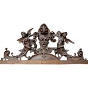 Ornately carved Armorial Overdoor with Grotesque flanked by Winged Angels