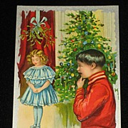 Antique Embossed Postcard-Young Girl Under Mistletoe w/Young Boy Looking On-Xmas Tree in Backg
