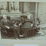 Photograph of Elderly Couple Sitting Outside Their Home