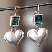 Designer earrings of silver heart and emerald color zircon.