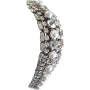 Dress up your wrist with this rhodium plated rhinestone encrusted bracelet with faux pearl ...