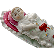 Early 20th century porcelain trinket Box in form of a swaddled baby doll