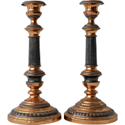 SALE A pair of brass and patinated metal candlesticks, mid 20th century.