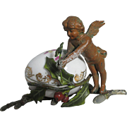 Winged Cherub on Holly Branch Holding a 4-leaf clover with Porcelain, Painted Metal Egg ...