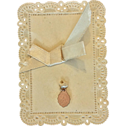 Tiny religious medal presented on lacy paper