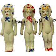 Trio of all bisque miniature bonnet head dolls