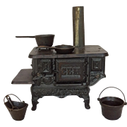 Antique doll-size cast iron stove with accessories