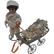 **A miniature antique doll with a carriage and baby***