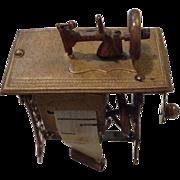 A tape measure shaped like a sewing machine. c 1900