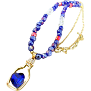 A Wine Bottle with Blue Crystal Heart Pendant and Crystal Bead Necklace