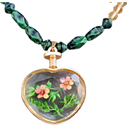 A Large Flower Enclosed Heart Pendant and Green Bead Necklace and Earrings