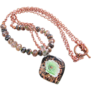 A Glass Spoon Pendant with a Green Swirled Flower Inside and Gold Sand Rondelles Necklace ...