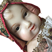 Wax Jesus baby in antique wooden crib - beautiful expression