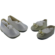 Two pair of white plastic doll shoes.