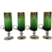 Set of four stemmed green and gold cordial or liquor glasses.