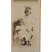 SOLD Studio Photograph-Two Cutie Pies In Sepia With Big Bow And Little Chair