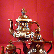 Three Graduated Barge Ware Teapots with Teapot Finials