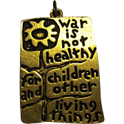 "ICONIC ""War is Not Healthy for Children & Other Living Things"" Pendant 1968"