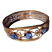 Art Deco Gold Tone Metal Ornate Filigree Bangle Bracelet With Blue Rhinestones