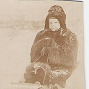 Photo Young Boy on Toboggan Wrapped in Bear Skin Outfit