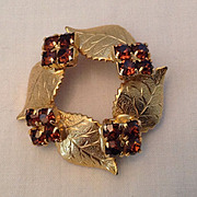 Gold Tone Circle pin with leaf motif and amber prong-set rhinestones