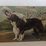 1908 Postcard with girl in lace bonnet and a large black and white dog.