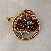 Gold tone circle pin with roses and turquoise colored rhinestones