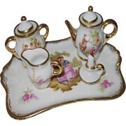 Miniature Limoges France tea set with tiny flowers and heavy gold tone trim
