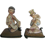 "SOLD Antique Pair 4"" Tall Seated Bisque Boy & Girl Figures Holding Dogs or Pincushions, circ"