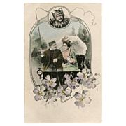 Antique Charles Scolik Postcard of Edwardian Couple in carriage overlooked by Bat Child