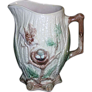 Large majolica pitcher s decorated with a robins nest on a tree branch with eggs ...