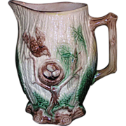 Large majolica pitcher decorated with robins nets with eggs in it on a tree branch