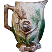 Large majolica pitcher decorated with a robins nest on a tree branch with eggs