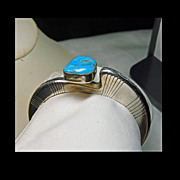 'Slice' Of Silver Cuff Bracelet with Deep Aqua Turquoise Set on  a Pedestal