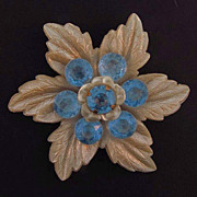 Large floral celluloid brooch with blue early plastic stones.