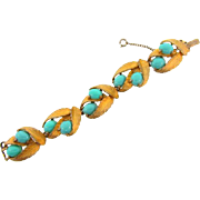 Signed Schiaparelli gold tone Leaf bracelet with blue cabochons