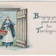 Pilgrim Maid with Harvest Basket Stands in Doorway Vintage Thanksgiving Postcard