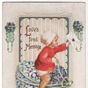 Child Sitting on a Tied Heart of Blue Flowers Vintage Valentine Postcard